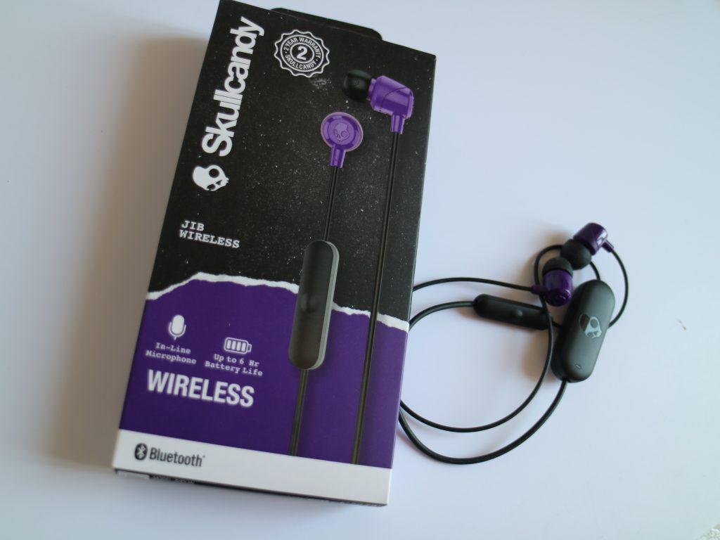 Gli auricolari Jib Wireless di Skullcandy sono appoggiati accanto alla loro confezione, dalla quale sono stati estratti. Sono viola e neri e sono arrotolati, ma si vede il simbolo del teschietto di Skullcandy sul trasmettitore