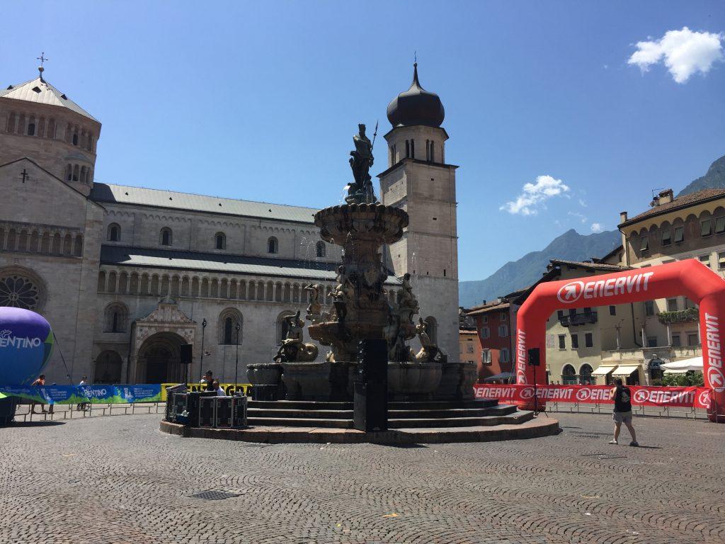 La piazza centrale di Trento sotto il sole cocente all'arrivo dei ciclisti della Moserissima. Sulla destra il pallone di Enervit, uno degli sponsor della cicloturistica