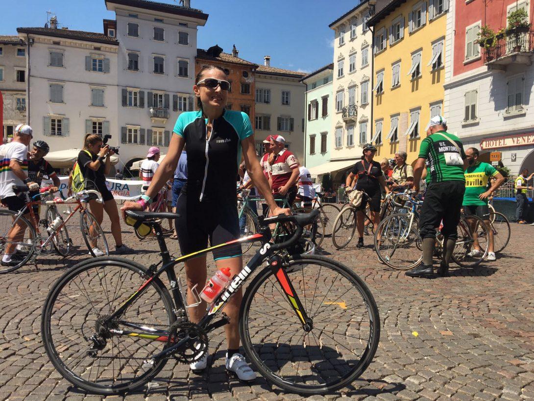 Daniela Schicchi all'arrivo dalla Moserissima in piazza a Trento, appoggiata alla sua bicicletta, sorride sotto lo striscione della Moserissima, davanti alla fontana della piazza