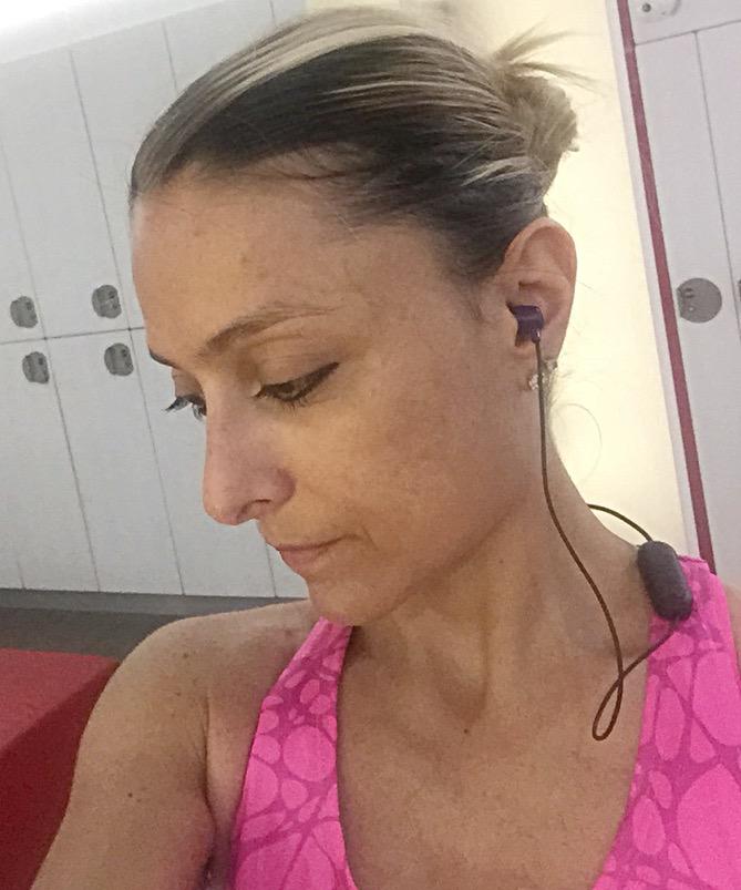 Daniela Schicchi in primo piano di profilo, indossa gli auricolari Skullcandy Jib Wireless mentre si prepara negli spogliatoi della palestra Virgin Active di Milano per allenarsi. Indossa una canotta Diadora fucsia