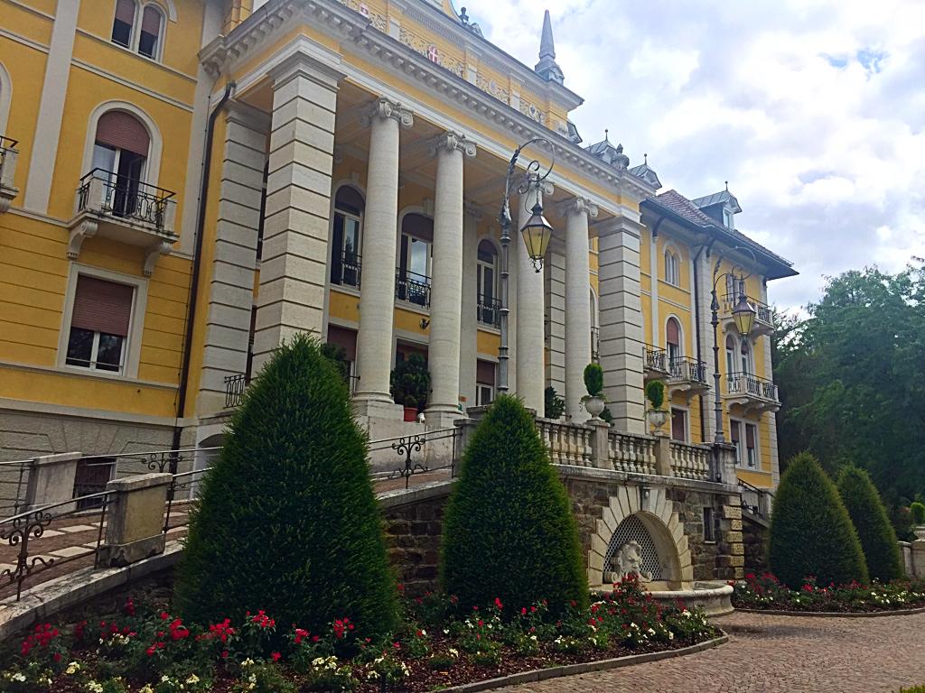 La facciata del Grand Hotel Imperial Levico Terme, con le sue colonne imperiali e la sua facciata color ocra, è immersa nel parco dell'hotel e accoglie imponente i visitatori