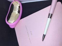 Sona è appoggiato sul tavolo accanto a un'agenda rosa e a una penna dello stesso colore