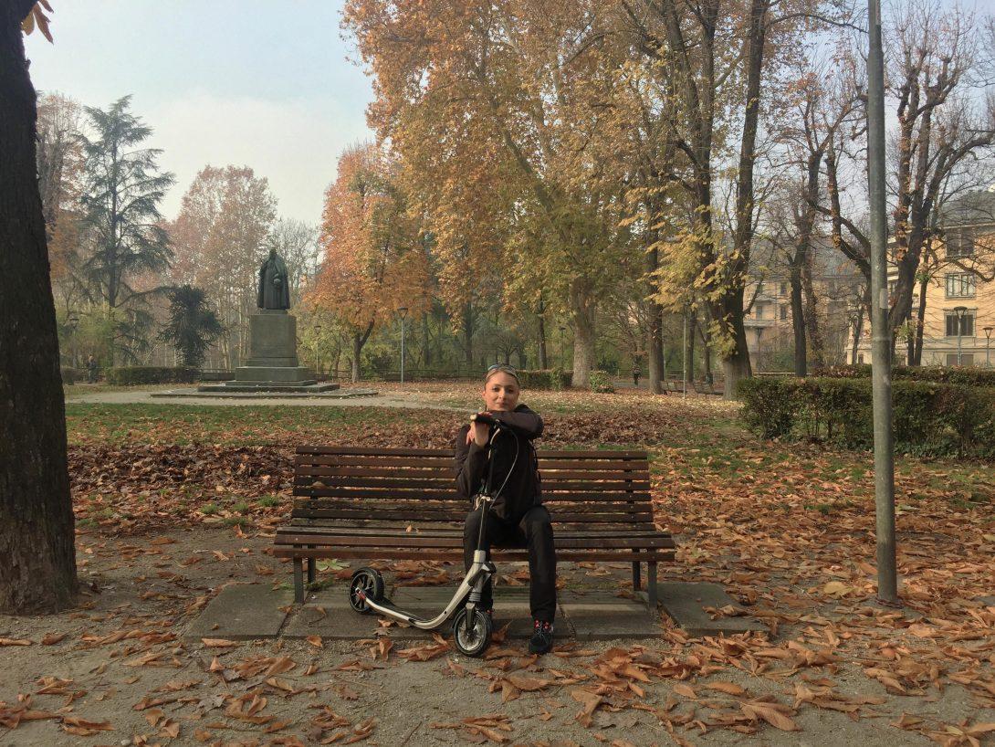 Daniela è seduta nel parco con tante foglie cadute, clima autunnale, e appoggia il viso sul manubrio del suo Town 9 di Decathlon