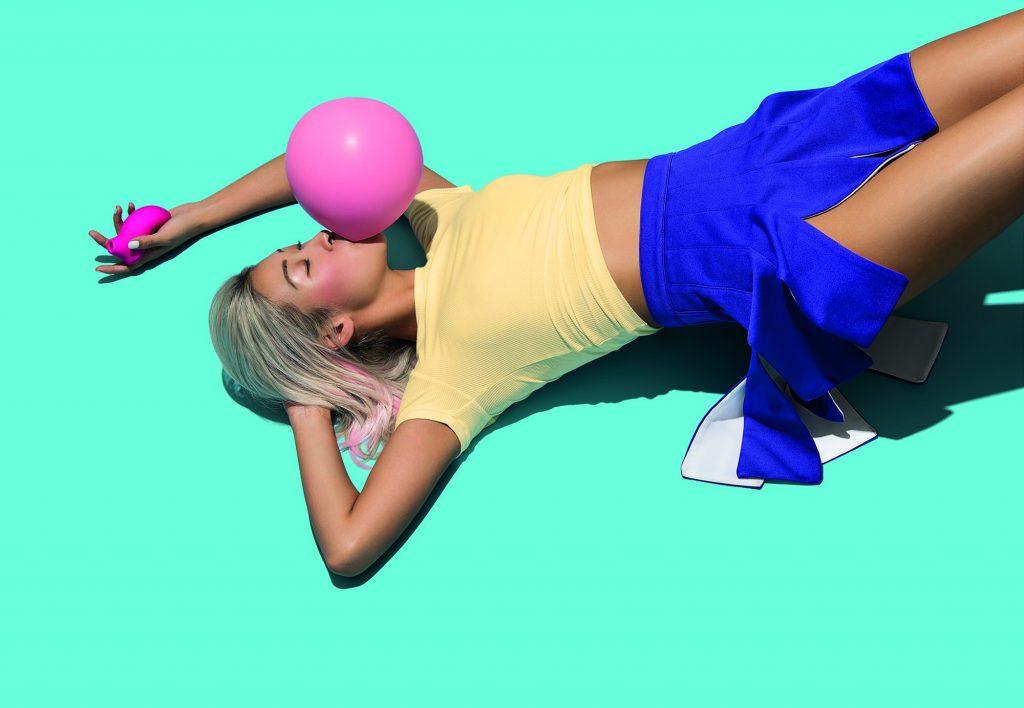 La campagna pubblicitaria di Pelo con una ragazza che fa un palloncino con una cicca e sdraiata a terra ha un viso compiaciuto, mentre tiene in mano Sona